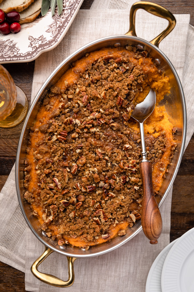 overhead of sweet potato casserole in a gratin pan on a Thanksgiving table