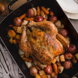 overhead view of a roasted chicken with root vegetables in a cast iron roasting pan