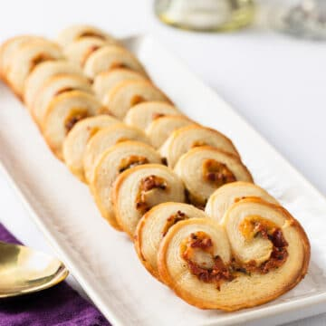 savory palmiers with bacon and gruyere on a white serving plate