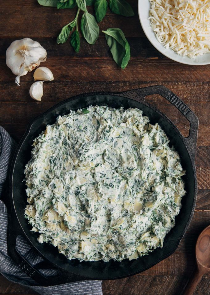 unbaked spinach artichoke dip in a round cast iron pan