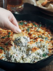 dipping crostini into cheesy warm spinach artichoke dip