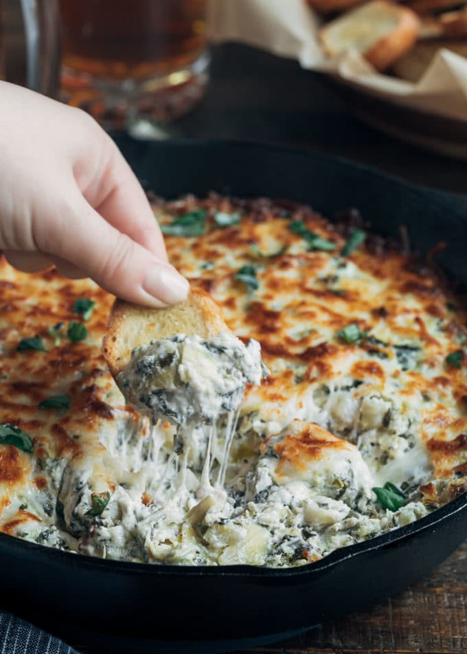 dipping crostini into cheesy warm spinach artichoke dip