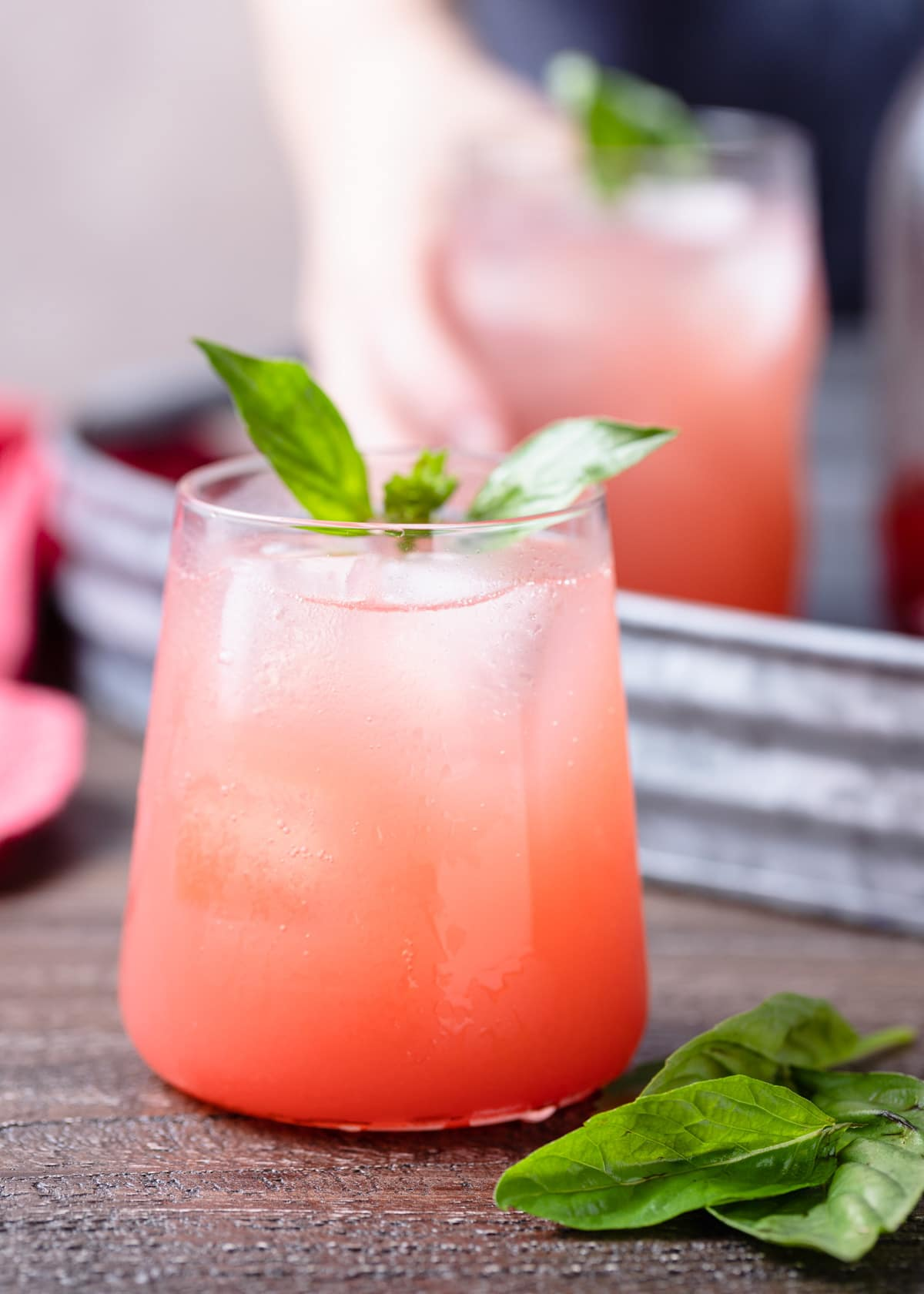 strawberry soda in a glass garnished with basil leaves on a wood board