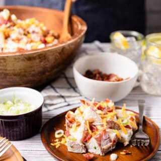 loaded potato salad served on a wooden plate, in front of a large wooden serving bowl