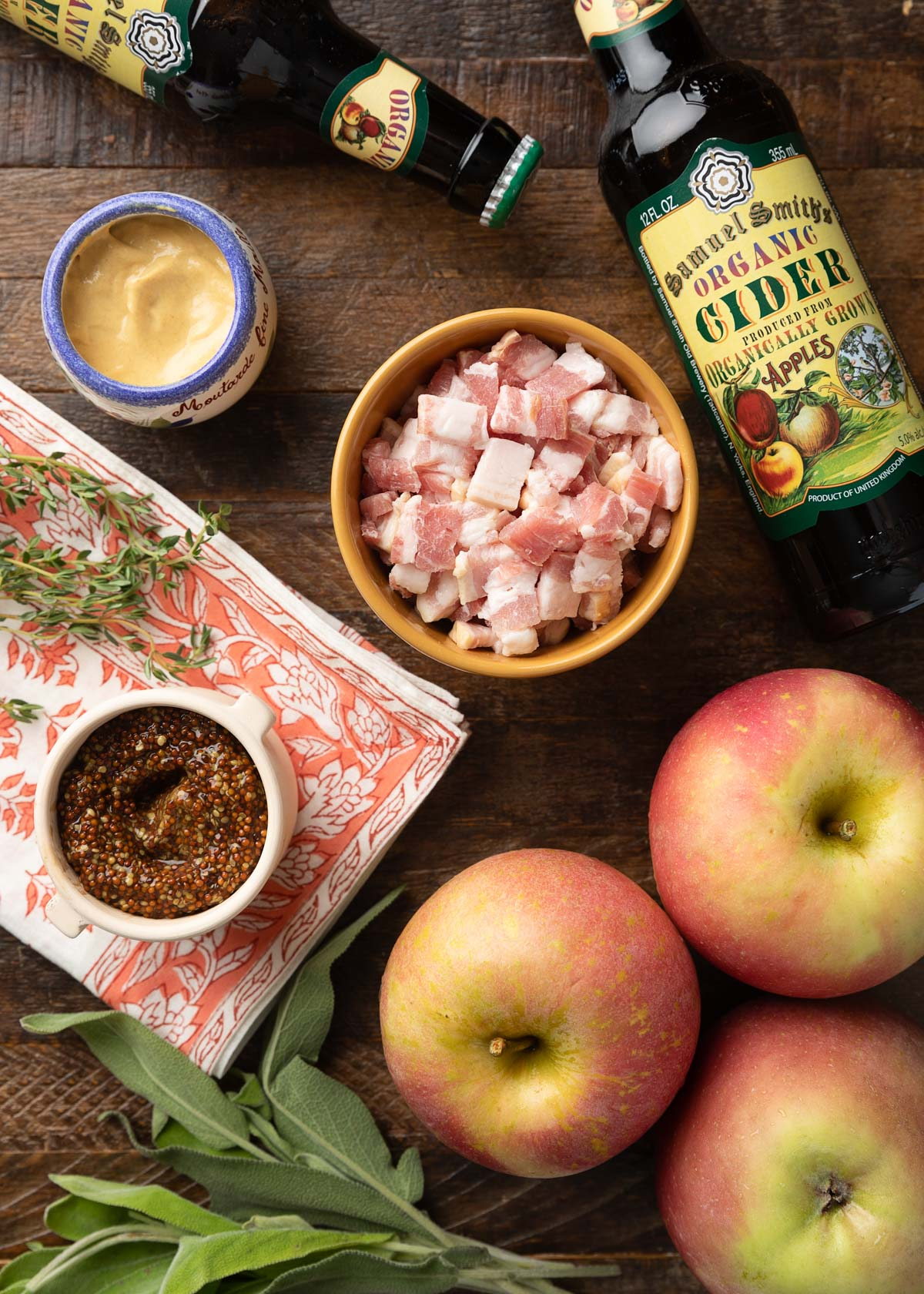 overhead viewe of bottles of hard cider, crocks of Dijon and grainy mustard, chopped bacon, apples, and herbs on a wood board