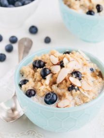 breakfast quinoa with blueberries and sliced almonds in a teal bowl