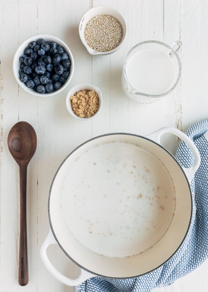 ingredients for blueberry breakfast quinoa on a white wood board