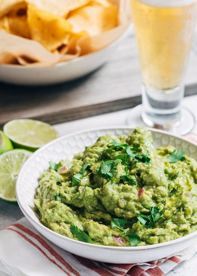 grilled guacamole in a serving bowl with a dish of tortilla chips