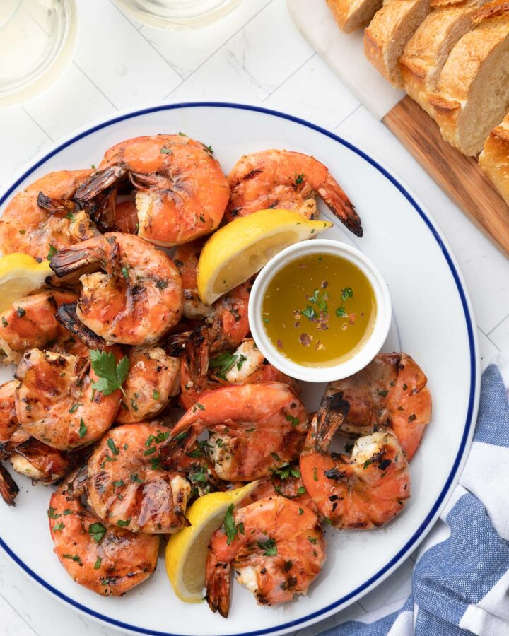 grilled lemon garlic shrimp on a blue rimmed white plate with lemon wedges and a bowl of dipping butter