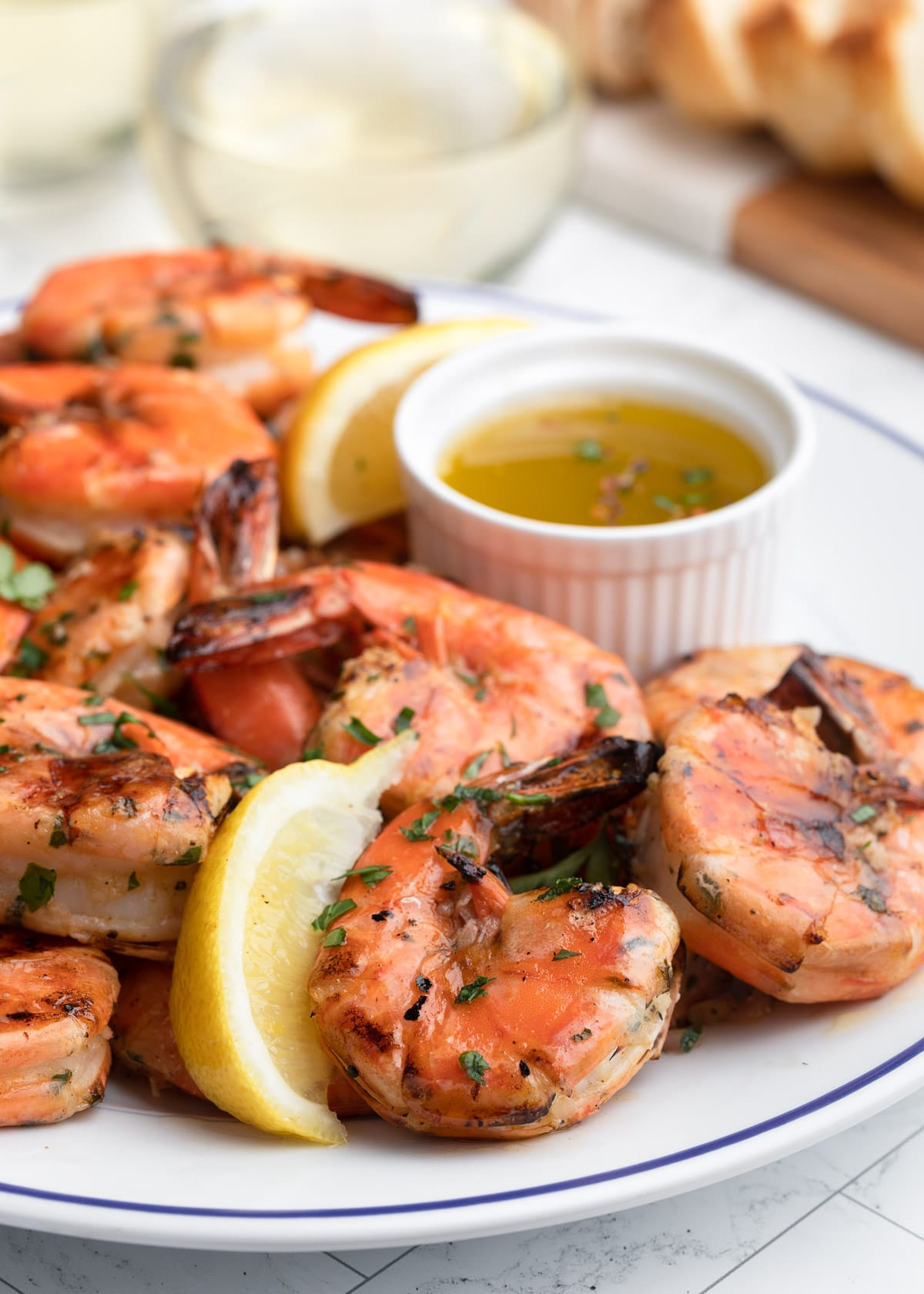 side view of lemon garlic grilled shrimp on a blue rimmed white plate with lemon wedges and dipping sauce