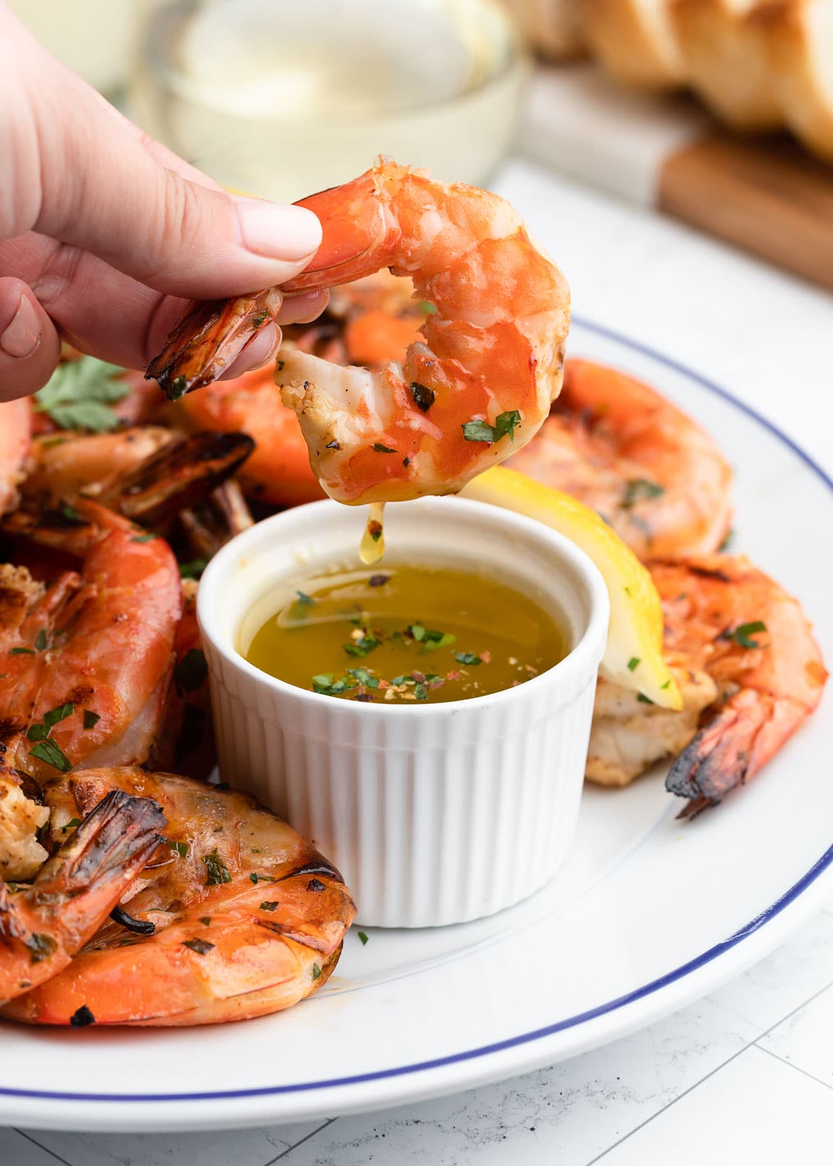 shelled grilled shrimp being dipped into a bowl of warm lemon garlic butter