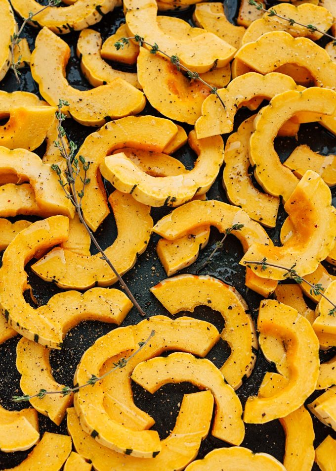 raw delicata squash rings on baking sheet with thyme