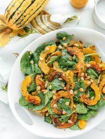 delicata squash salad with baby spinach and brown butter vinaigrette in a white serving bowl