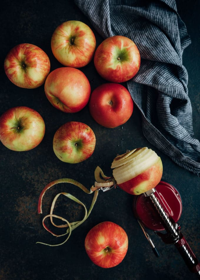 apples on a dark board with an apple peeler tooler