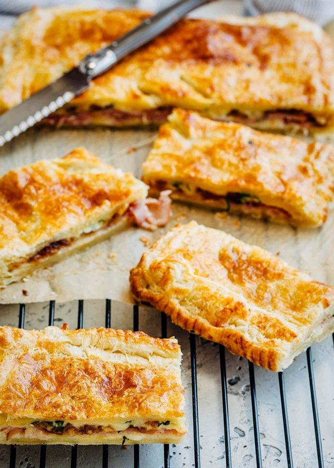 strips of ham and cheese puff pastry on a cooling rack