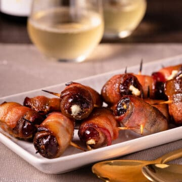 a platter of devils on horseback on a cloth table runner with glasses of white wine