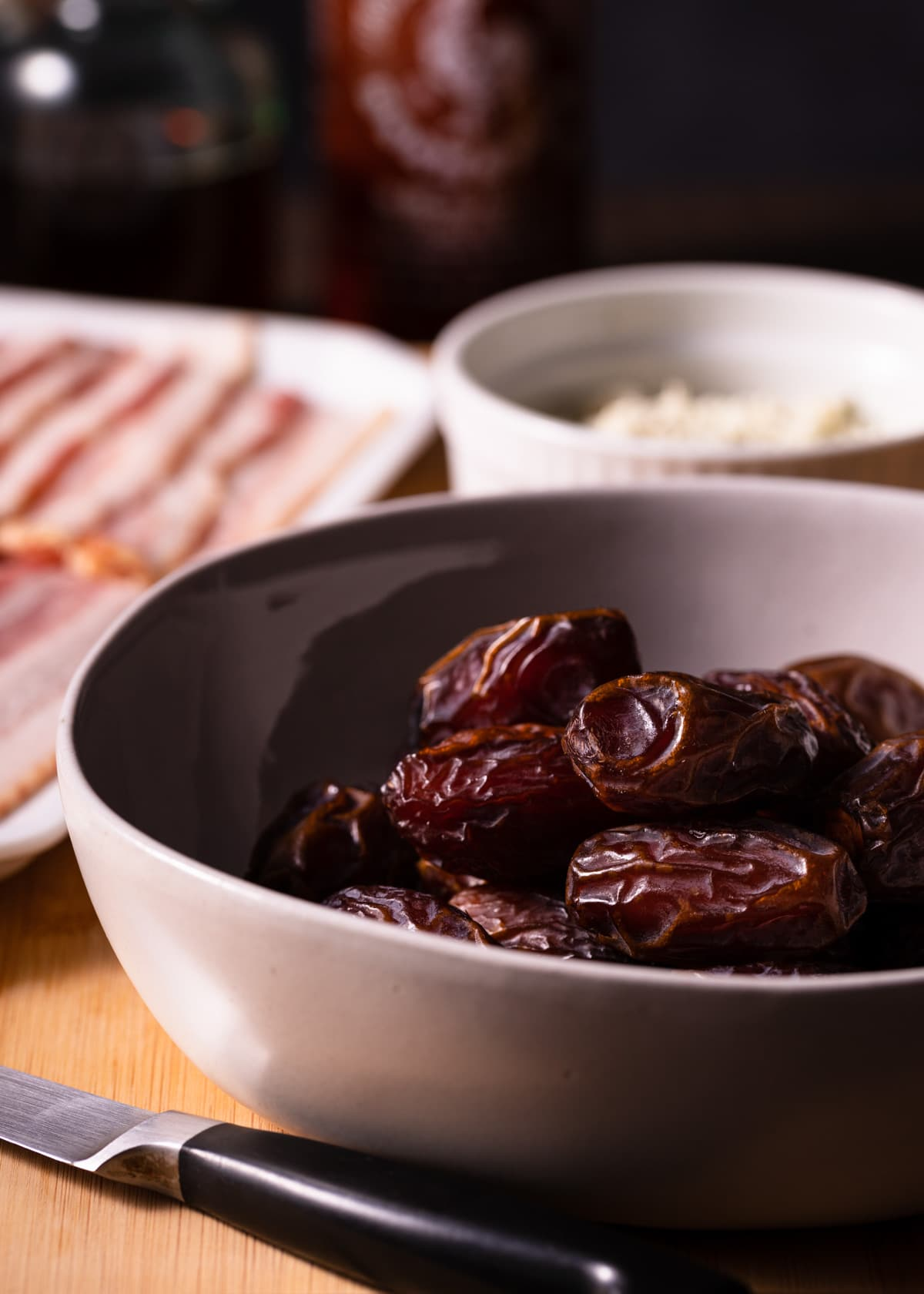 a bowl of medjool dates with a bowl of crumbled blue cheese and a platter of raw bacon in the background
