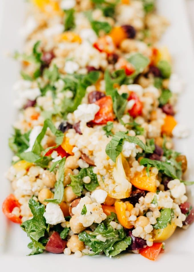 side view of israeli couscous salad with arugula, tomatoes, and feta on a white platter