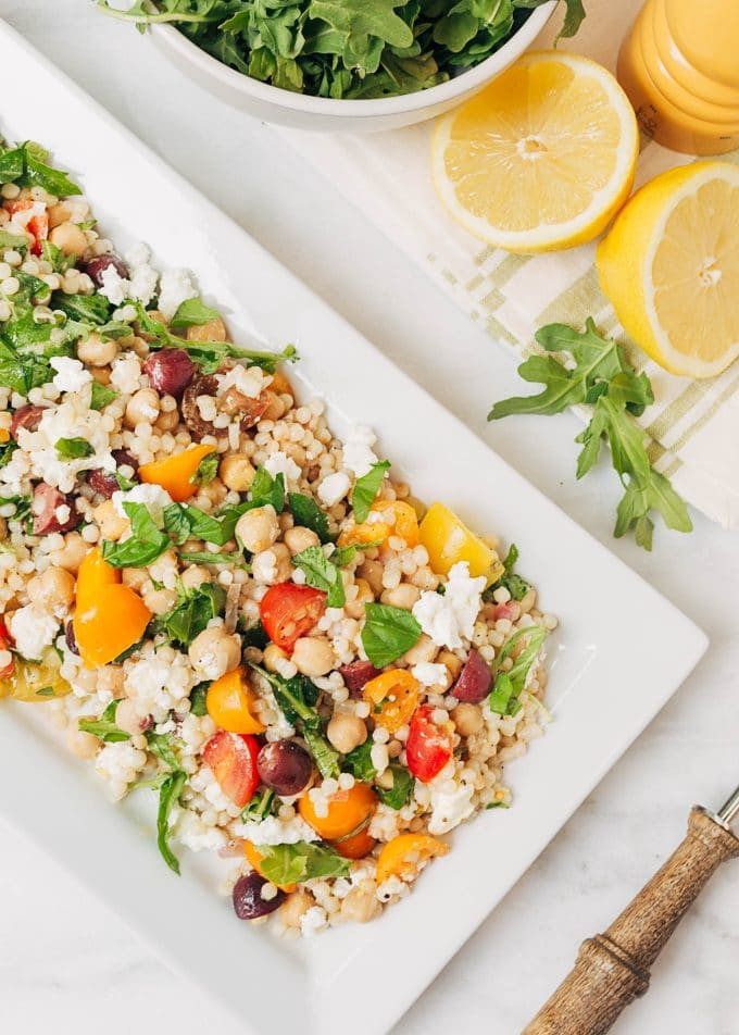 mediterranean pearled couscous salad on a white platter