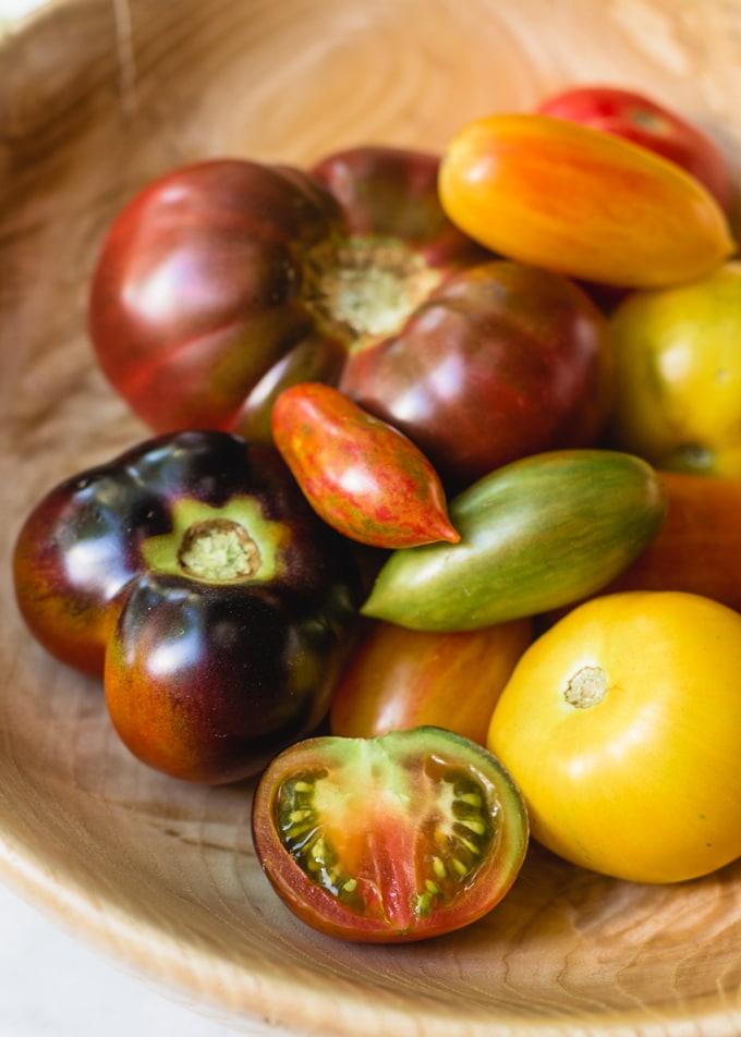 assorted heirloom tomatoes in a hand-carved wooden bowl