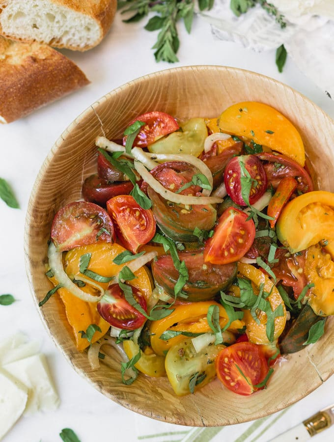 heirloom tomato salad with onions and basil in a wooden bowl