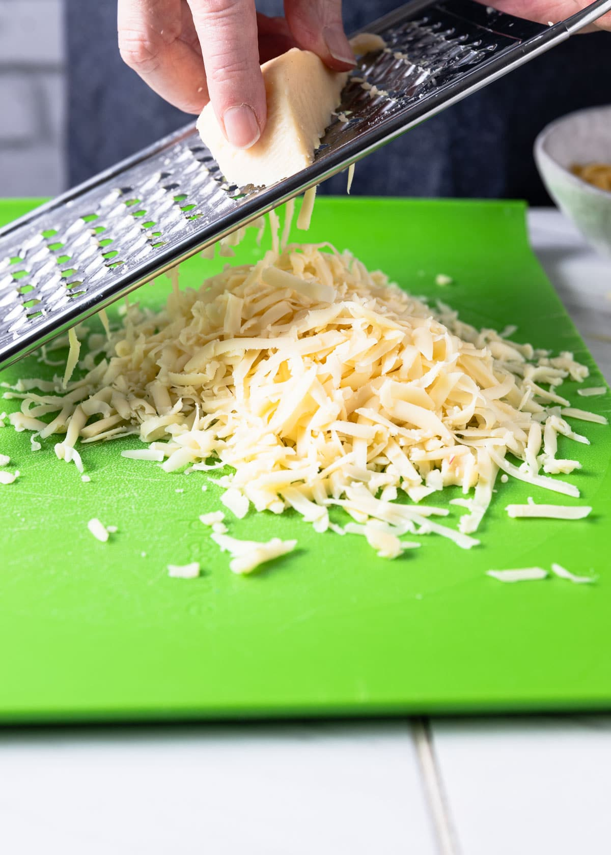 grating fontina cheese on a green cutting board