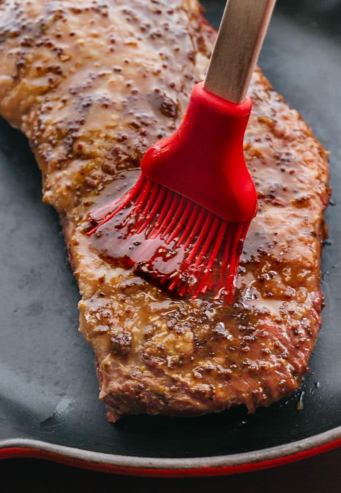 brushing whiskey mustard glaze onto cooked corned beef