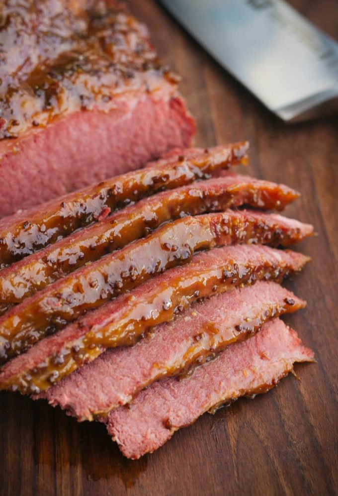 sliced beer braised corned beef with whiskey mustard glaze on a wood board