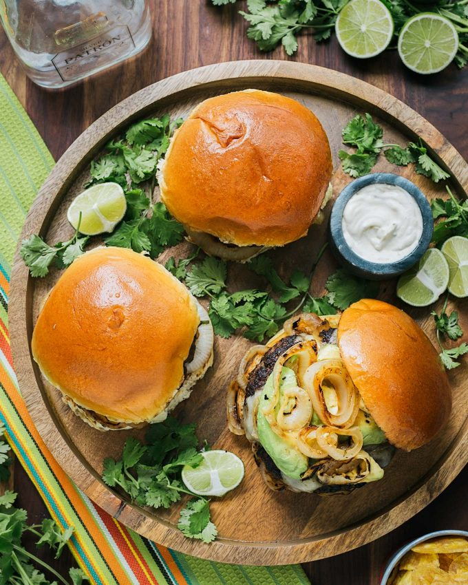 mojo beef burgers on serving tray with a bowl of tequila lime aioli