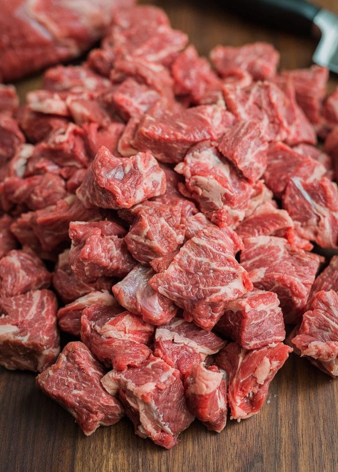 chuck beef cut into cubes for grinding on a cutting board
