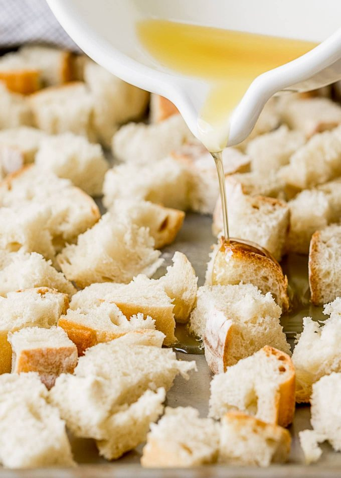 pouring garlic butter onto French bread cubes for croutons