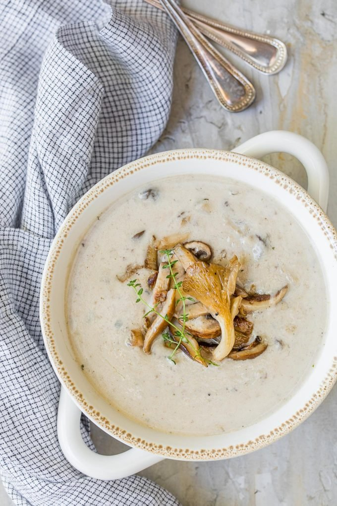 overhead photo of homemade cream of mushroom soup in a white bowl with a blue checked napkin