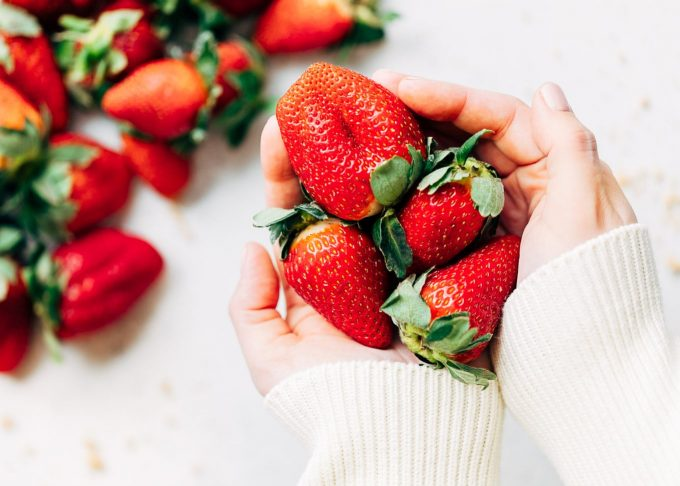 California Giant Berry Farms strawberries held in hands wearing an ivory sweater [sponsored]