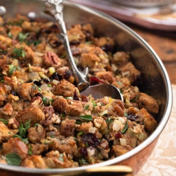 side view of baked cranberry pecan stuffing in a gratin dish with a silver serving spoon
