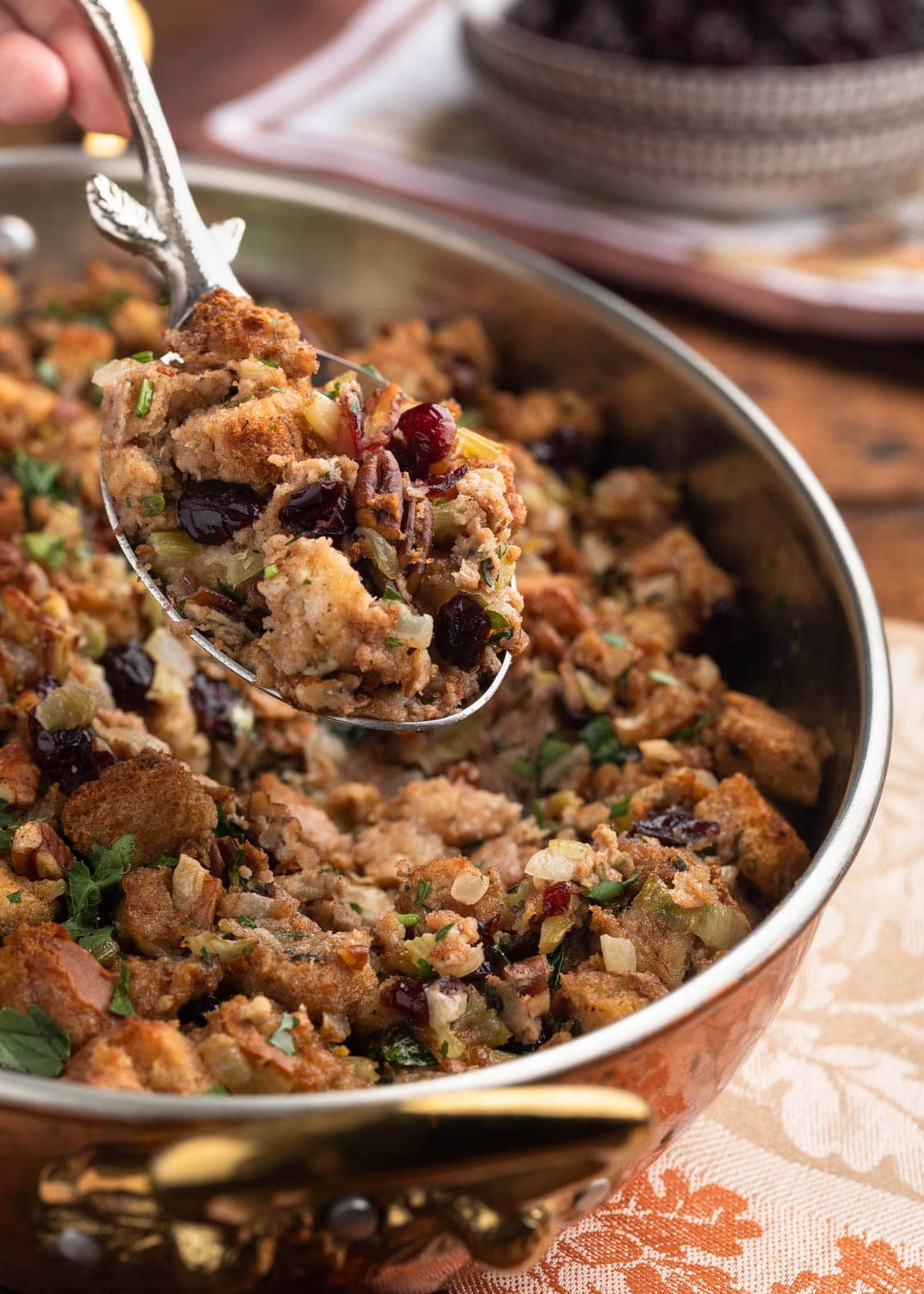 silver serving spoon holding a scoop of cranberry pecan stuffing over the baking dish
