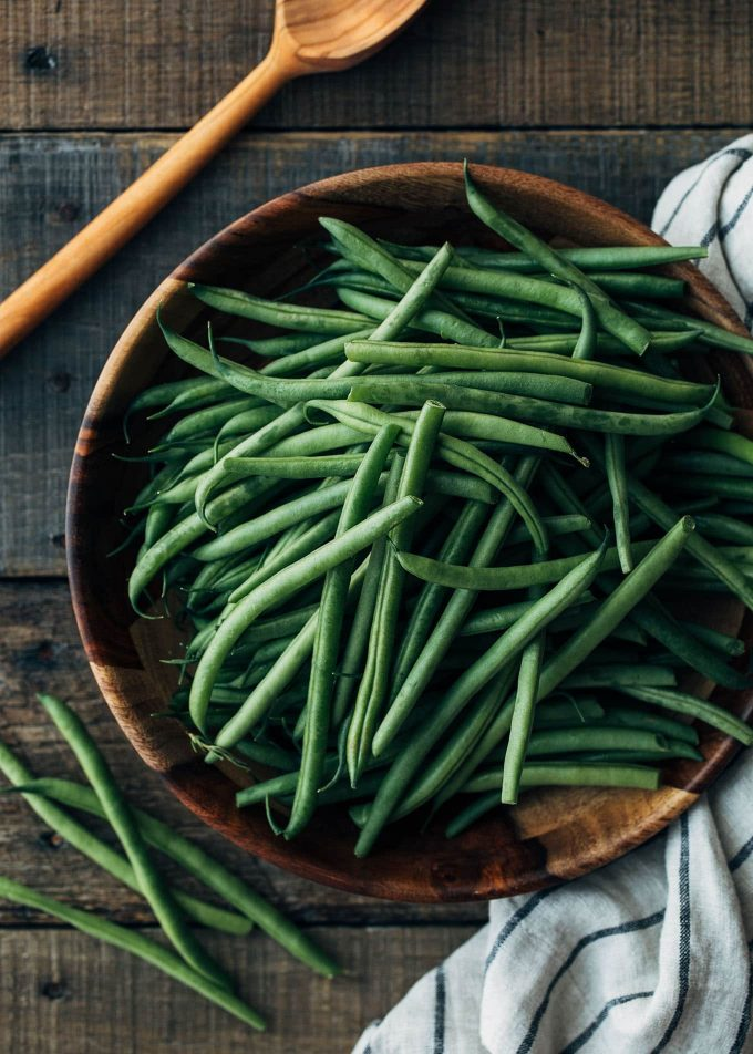 uncooked haricots verts in a wood bowl on a rustic wood board