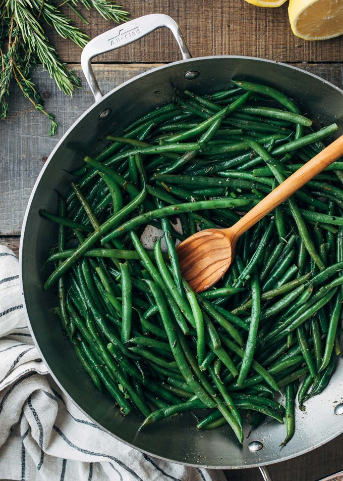 haricots verts in an all clad pan with brown butter and a wooden spoon
