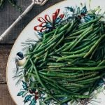haricots verts on a Christmas serving platter with silver serving tongs