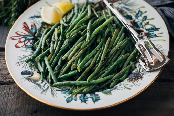 haricots verts on a christmas pattern serving platter with lemon wedges and silver tongs