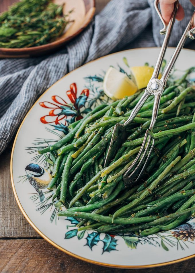 brown butter green beans being served with silver serving tongs from a Christmas platter