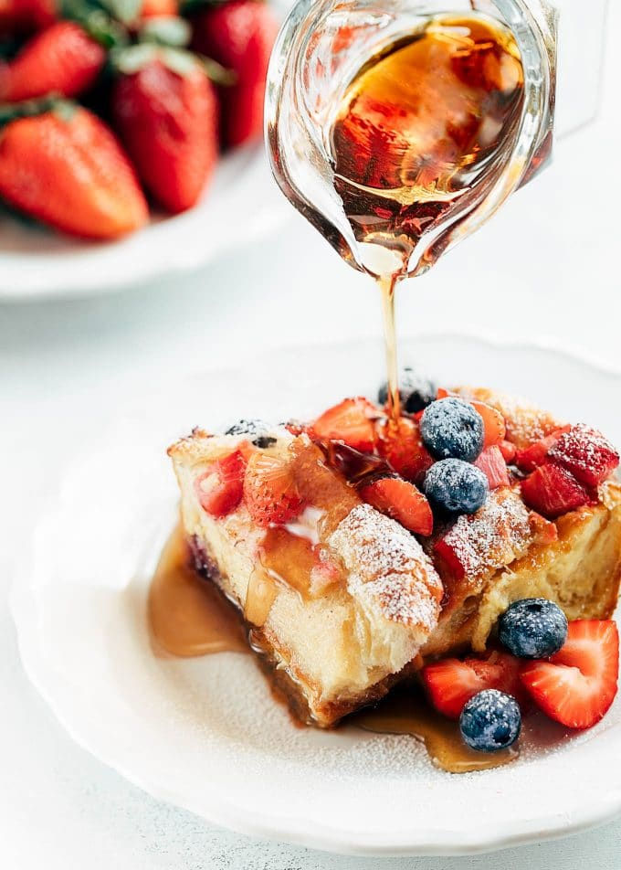 wedge of berry croissant baked french toast on a white plate with rum maple syrup poured from a glass creamer [sponsored]