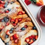 overnight croissant baked french toast with strawberries and blueberries in a stub casserole dish