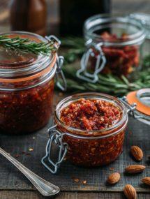 pesto rosso (sun-dried tomato pesto) in glass storage jars on a wood board