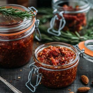 pesto rosso (sun-dried tomato pesto) in glass storage jars on a wood board