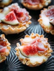 miniature phyllo brie bites with figs and prosciutto on a serving tray