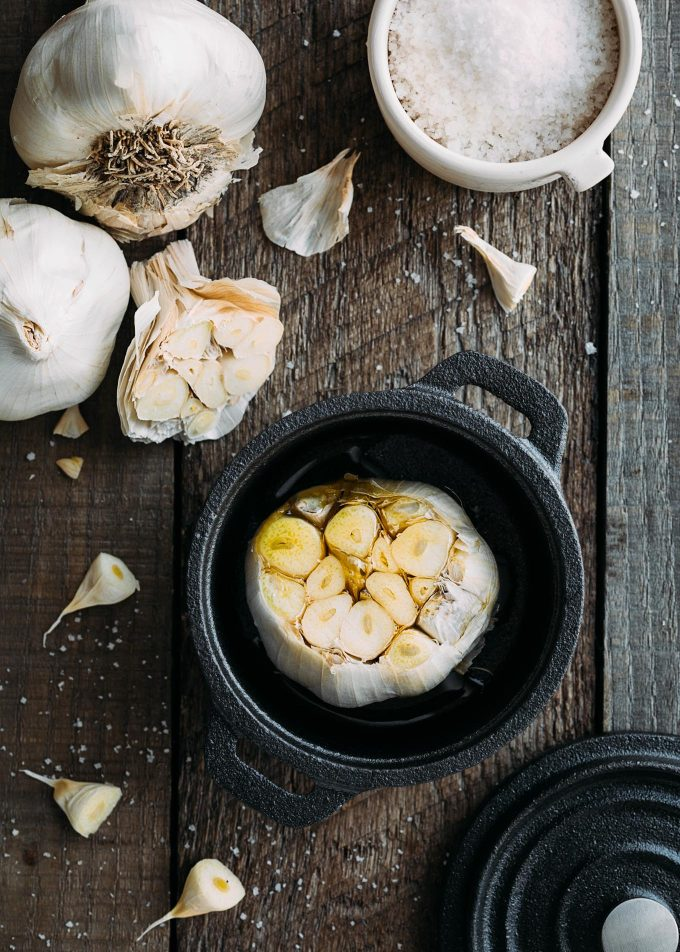trimmed head of garlic in a cast iron cocotte with olive oil