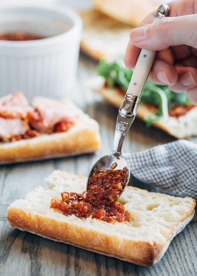 spooning pesto rosso onto ciabatta bread