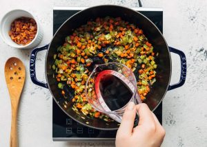 deglazing a pot of sautéed vegetables with red wine