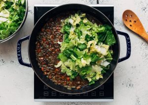 chopped raw escarole added to a pot of lentil soup