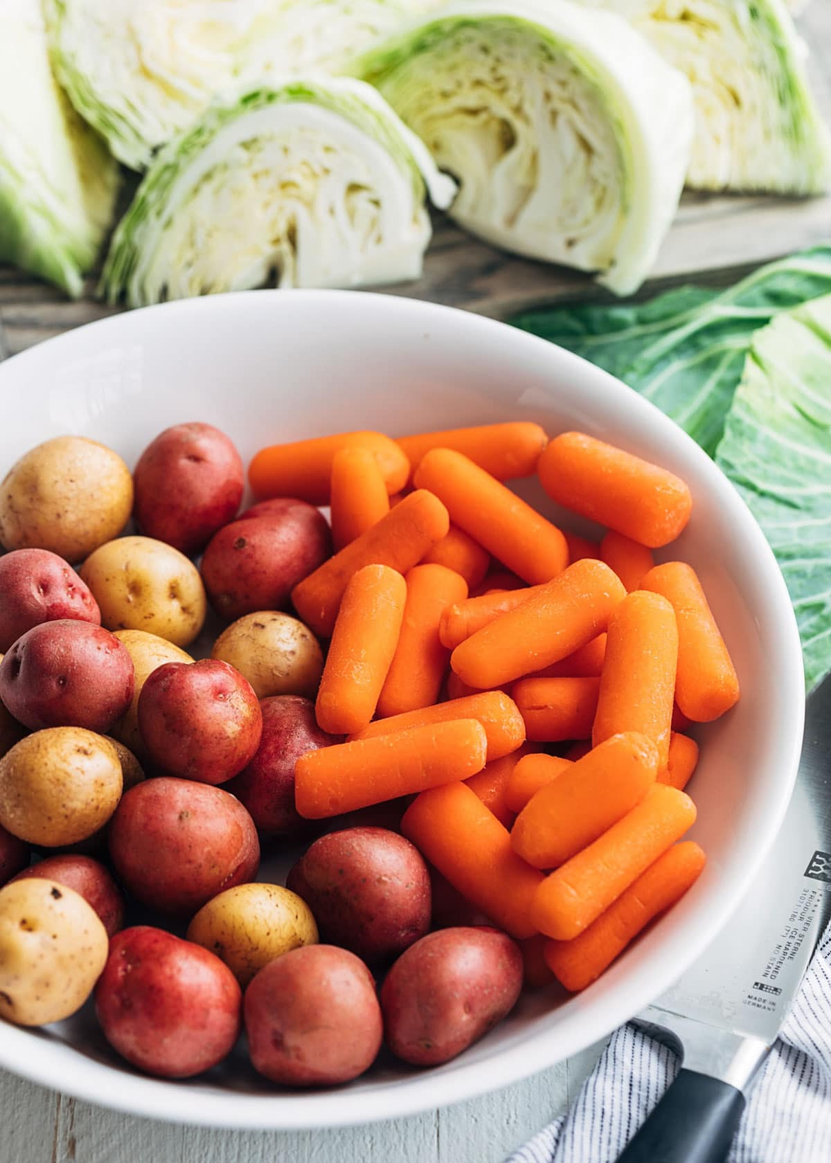 small potatoes and baby carrots in a white bowl surrounded by green cabbage wedges